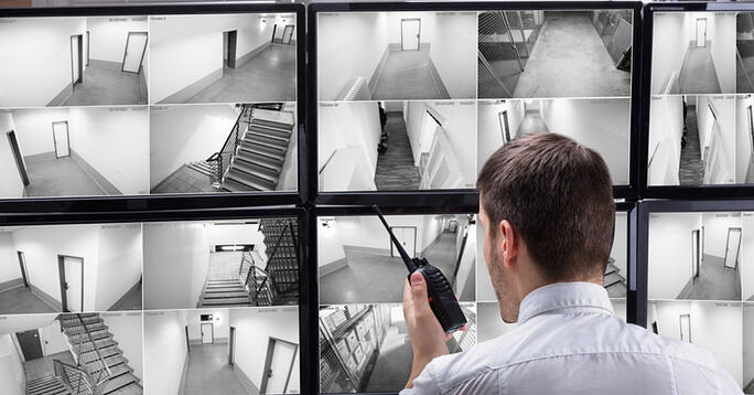 Security guard monitoring CCTV footage - physical security - 24By7Security