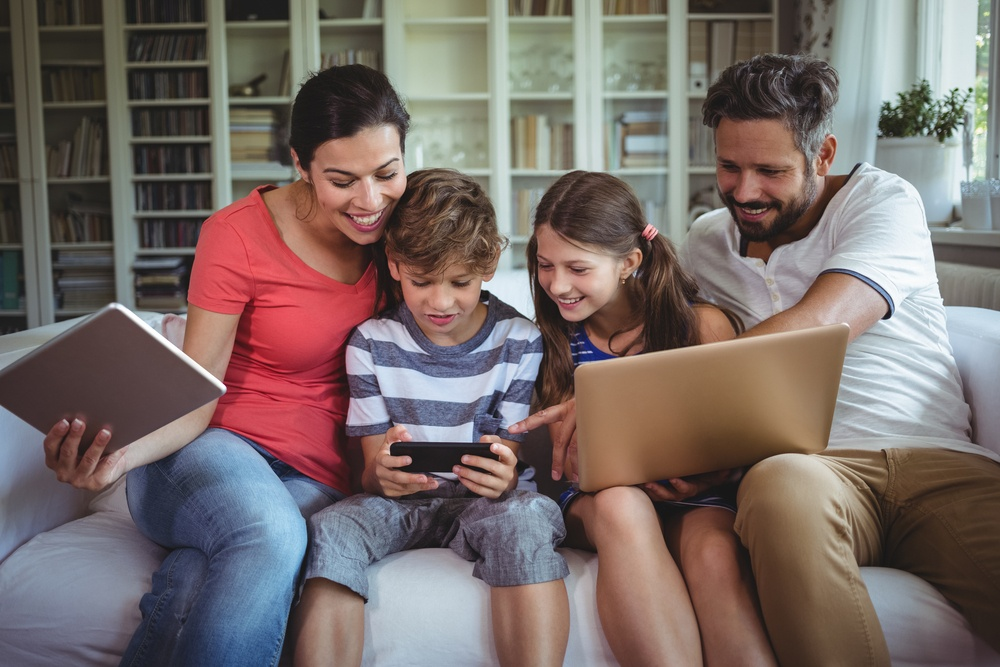 Happy family sitting on sofa and using laptop, mobile phone and digital tablet at home